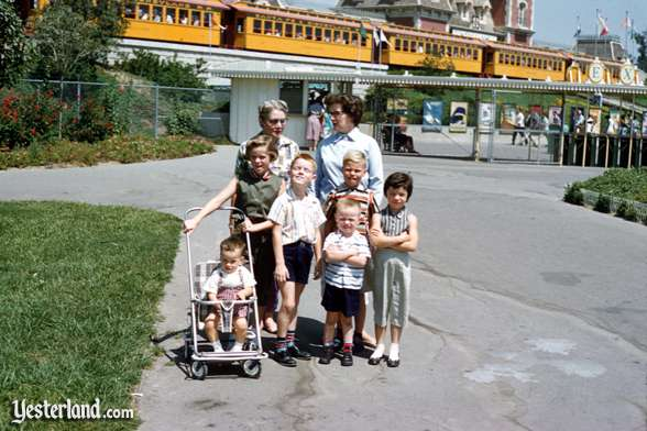 A family poses outside of Disneyland with the Passenger Train in the background